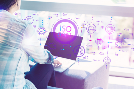 ISO 9001 with woman using her laptop in her home office Stok Fotoğraf