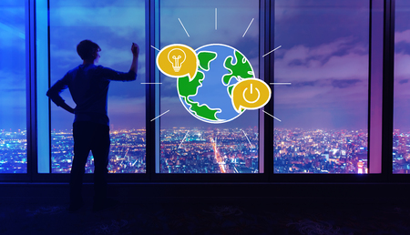 Earth hour with man writing on large windows high above a sprawling city at night Stock Photo