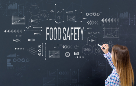 Food safety with young woman writing on a blackboard