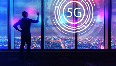 5G network with man writing on large windows high above a sprawling city at night
