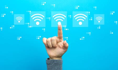 Wifi-Konzept mit Hand auf blauem Hintergrund Standard-Bild