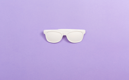 Funky party opaque glasses on a purple paper background