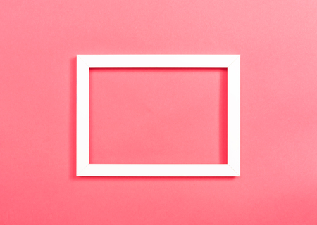 Empty photo frame on a pink paper background