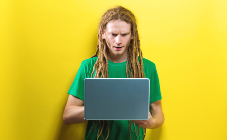 Young man using a laptop on a solid color background Stock Photo