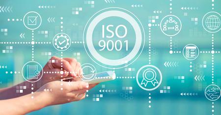 ISO 9001 mit einer Person, die ein weißes Smartphone hält Standard-Bild