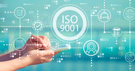 ISO 9001 with person holding a white smartphone Standard-Bild - 118613415