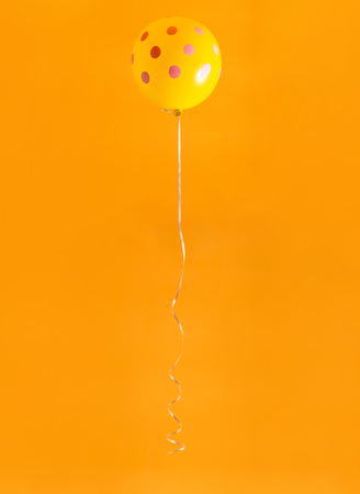 Party Balloon floating on a yellow background Banco de Imagens