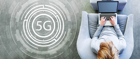 5G network with man using a laptop in a modern gray chair