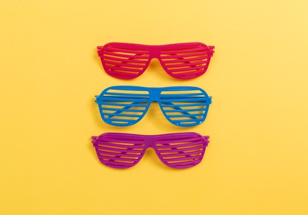 Shutter shade party glasses on a yellow paper background