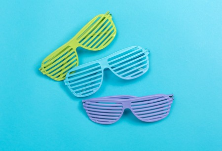 Shutter shade party glasses on a blue paper background