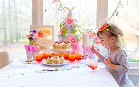 Little toddler girl eating dessert after Easter dinner