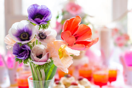 Vase of spring flowers on a dessert table Stock Photo