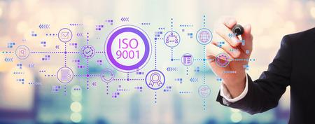 ISO 9001 mit Geschäftsmann auf verschwommenem abstraktem Hintergrund Standard-Bild