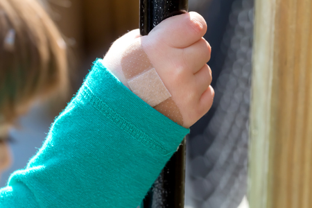 Toddler boy with a bandage on his hand at a playground