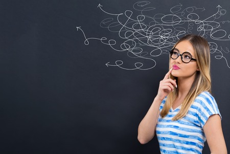 Solving a problem concept with young woman in front of a blackboard
