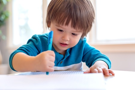 Toddler boy drawing with pen and paper at his desk