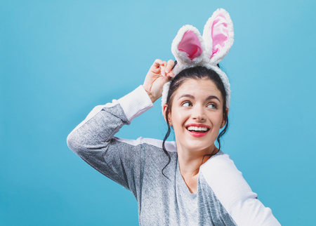 Young woman with Easter rabbit ears on a blue background