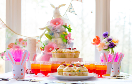 Dessert table with cupcakes and flowers Easter party theme Foto de archivo
