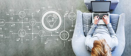 LiFi-thema met een man die een laptop gebruikt in een moderne grijze stoel Stockfoto