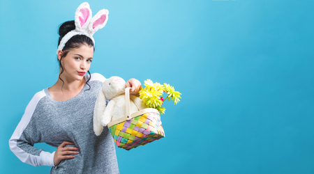 Young woman with Easter basket on a blue background