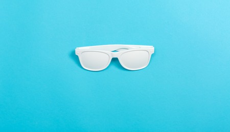 Funky party opaque glasses on a blue paper background