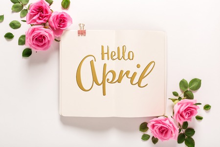 Hello April message with roses and leaves top view flat lay