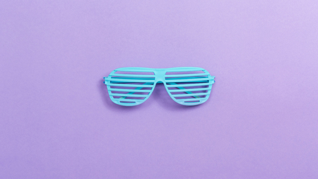 Shutter shade party glasses on a purple paper background