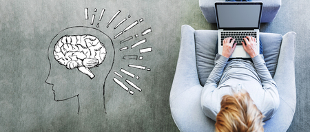 Brain illustration with man using a laptop in a modern gray chair Reklamní fotografie