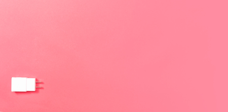 Charger plug adapter on a pink paper background
