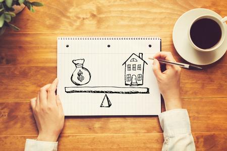 Maison et argent sur la balance avec une personne tenant un stylo sur un bureau en bois Banque d'images