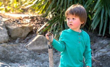 Toddler boy digging with a shovel outside Stock fotó