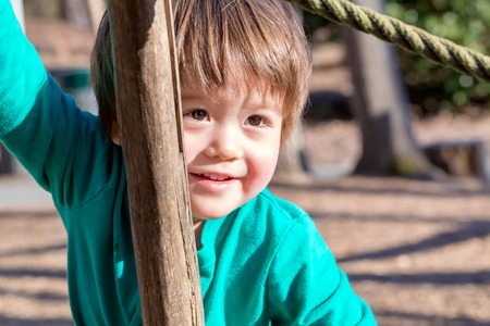 Happy toddler boy playing outside at a playground Stock fotó