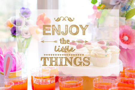 Enjoy the little things with dessert table with cupcakes and flowers Stock Photo