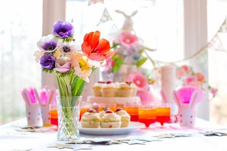 Stół deserowy z babeczkami i kwiatami Motyw przyjęcia wielkanocnego Zdjęcie Seryjne