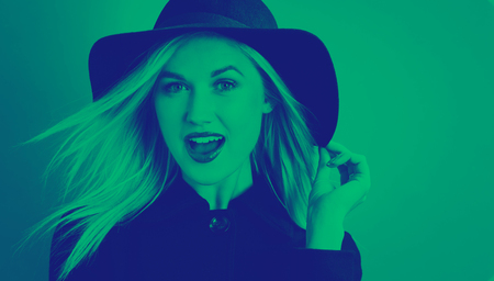 Beautiful young blonde woman in a black coat and hat with duotone Stock Photo