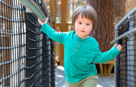 Toddler boy playing outside at a playground