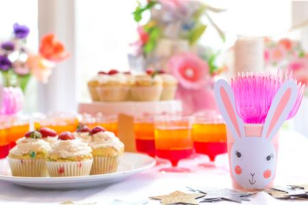 Tavolo da dessert con cupcakes e fiori a tema festa di Pasqua