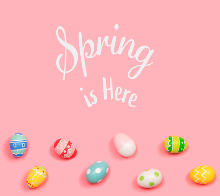 Spring is here message with Easter eggs on a pink background Stock Photo