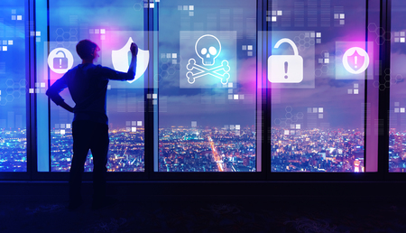 Virus and scam theme with man writing on large windows high above a sprawling city at night Imagens