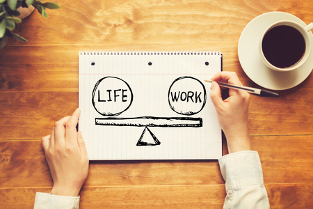 Life and work balance with a person holding a pen on a wooden desk Фото со стока