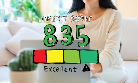 Excellent credit score theme with woman using her laptop in her home office