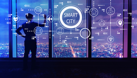 Smart city concept with man writing on large windows high above a sprawling city at night