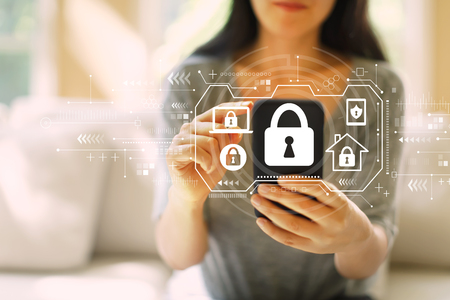 Security theme with woman using her smartphone in a living room