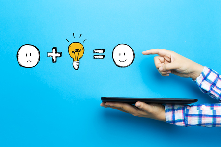 Good idea equals happy with a tablet computer on a blue background