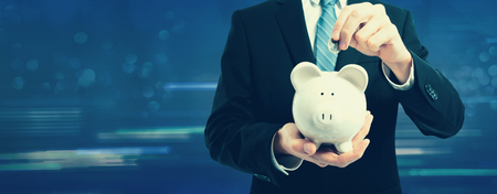 Businessman with a piggy bank on a dark blue Фото со стока