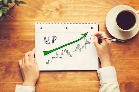 Market up trend chart with a person holding a pen on a wooden desk