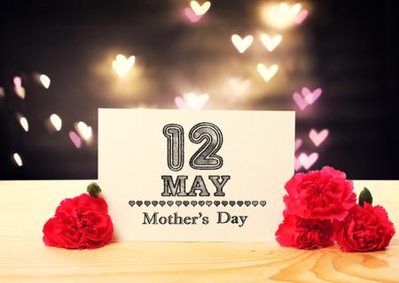 Kartka z wiadomością na Dzień Matki z kwiatami goździków i światłami w kształcie serca