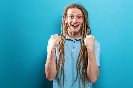 Successful young man with dreadlocks on a solid background