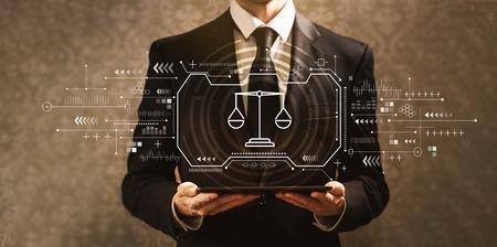 Motyw sprawiedliwości z biznesmenem trzymającym komputer typu tablet