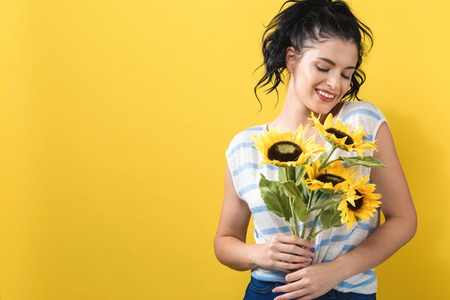 Young woman with sunflowers on a yellow background 版權商用圖片